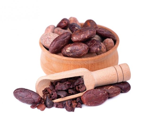 Obrane kakaowe ziarna w drewnianym pucharze, odosobnionym. prażone i aromatyczne ziarna kakaowe w drewnianej łyżce, naturalna czekolada.