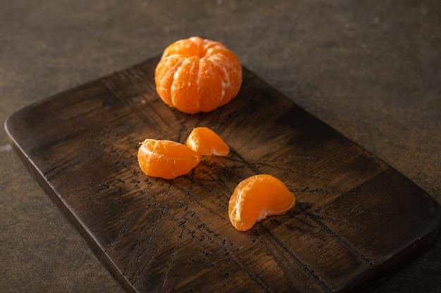 Obrane mandarynki i plastry na drewnianej desce z teksturą, selektywna ostrość, miejsce