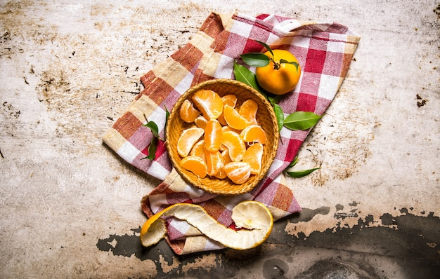 Obrane mandarynki w misce na tkaninie na rustykalnym stole. widok z góry
