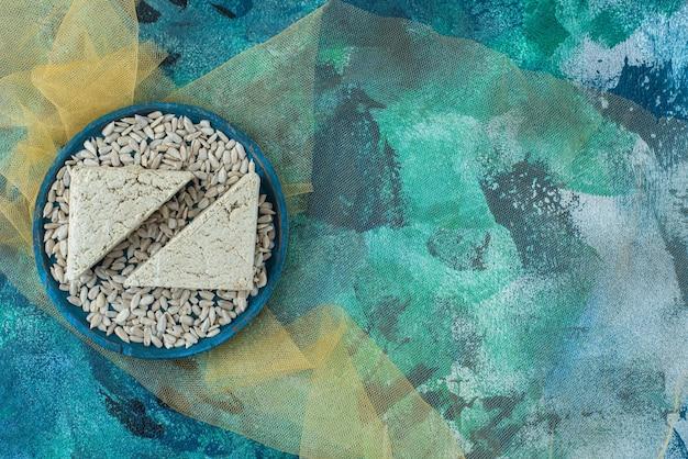 Obrane nasiona słonecznika i pokrojona chałwa na drewnianym talerzu na tiulu, na niebieskim stole.