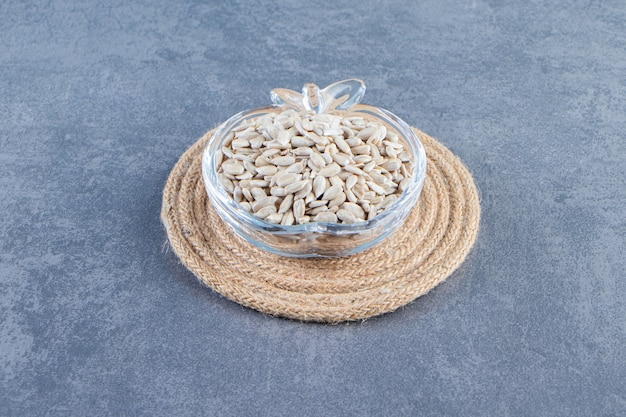 Obrane nasiona słonecznika w szklanej misce na podstawce na marmurowej powierzchni