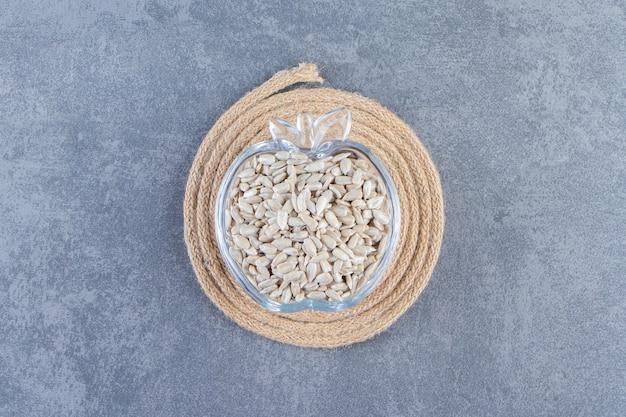 Obrane nasiona słonecznika w szklanej misce na podstawce, na marmurowym tle.