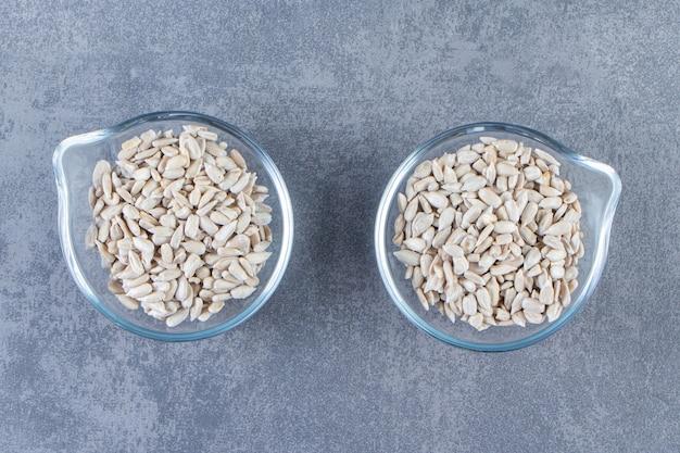 Obrane nasiona słonecznika w szklanych miseczkach, na marmurowej powierzchni
