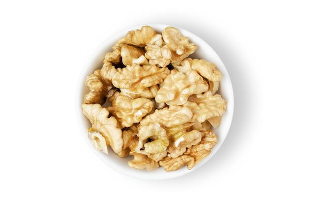 Obrane orzechy włoskie w misce. pojedynczo na białym tle. orzechy zawierają białko roślinne i witaminy. dla zdrowej i wegetariańskiej diety.