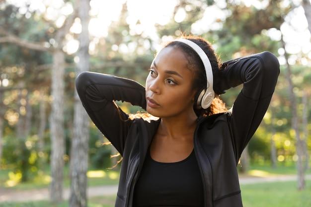 Obraz 20-letniej biegaczki w czarnym dresie i słuchawkach, spacerującej po zielonym parku