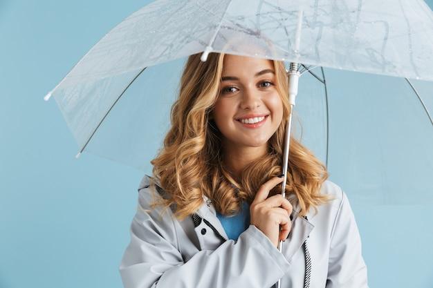 Obraz 20s blond radosnej kobiety noszącej płaszcz przeciwdeszczowy stojącej pod przezroczystym parasolem