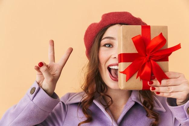 Obraz 20s urodziny kobieta z długimi włosami, uśmiechając się i trzymając pudełko, stojąc na białym tle