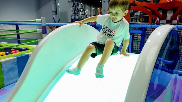 Obraz 3-letniego chłopca jadącego na zjeżdżalni na placu zabaw w centrum handlowym