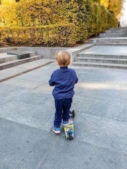 Obraz 3-letniego chłopca jeżdżącego na skuterze w jesiennym parku