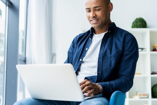Obraz african american biznesmen pracy na swoim laptopie. przystojny młody mężczyzna przy biurku.