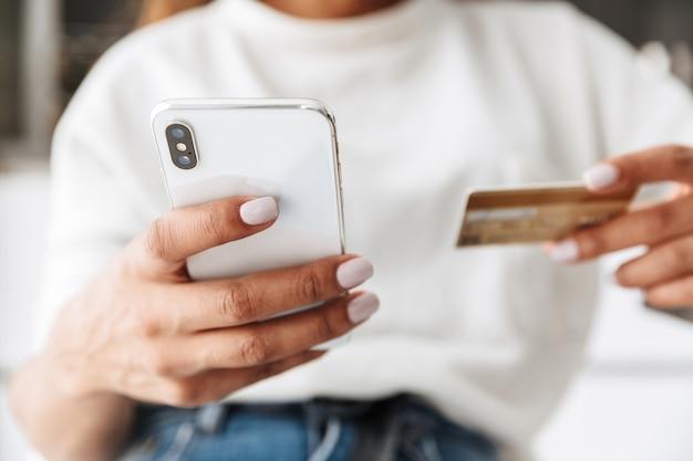Obraz afroamerykanki 20s przy użyciu telefonu komórkowego i karty kredytowej, siedząc przy stole w jasnym salonie