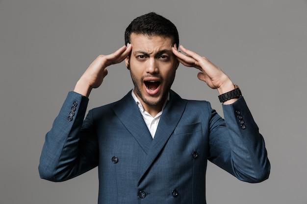 Obraz agresywnego krzyczącego biznesmena z bólem głowy pozowanie na białym tle nad szarej ściany.