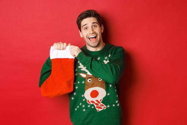 Obraz atrakcyjnego wesołego mężczyzny w swetrze, trzymającego skarpetę świąteczną z prezentami, z okazji ferii zimowych, stojącego na czerwonym tle.