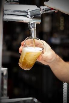 Obraz barmana wlewającego piwo z beczki do szklanki w pubie lub restauracji