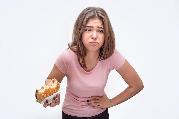 Obraz beka młodej kobiety. jedną rękę trzyma na brzuchu, a drugą z burgerem. model czuje się chory.