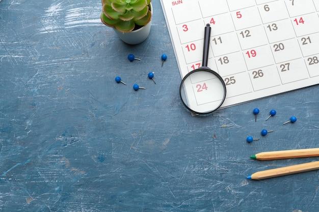 Obraz biznesu i spotkań. kalendarz przypominający o ważnym spotkaniu i lupę