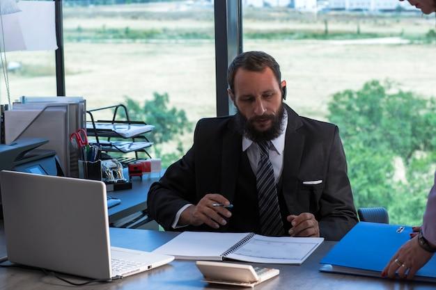 Obraz brodaty mężczyzna ubrany w krawat koszulę i czarny garnitur siedzi w biurze przy stole, trzyma w ręku długopis. człowiek z dokumentów i folderów pracy z laptopem przy biurku w biurze. dokument szuka prawnika