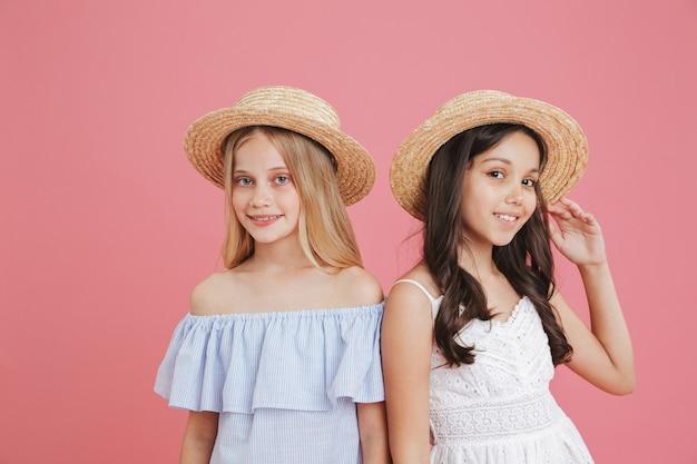 Obraz brunetka i blondynka letnie dziewczyny ubrane w sukienki i słomkowe kapelusze, uśmiechając się i patrząc na kamery, na białym tle nad różowym tle