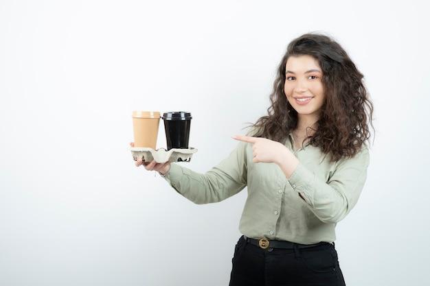 Obraz brunetki stojącej i wskazującej na dwie filiżanki w kartonie.