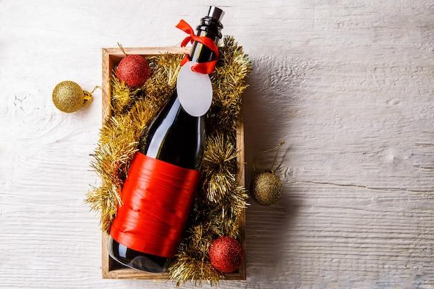 Obraz butelki wina z pustą kartą w pudełku z blichtr, bombki na białym stole