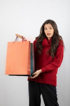 Obraz całkiem młoda kobieta na białym tle nad białą ścianą trzymającą torby na zakupy.