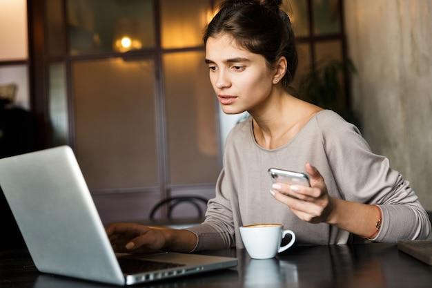 Obraz całkiem młoda kobieta siedzi w pomieszczeniu kawiarni przy użyciu komputera przenośnego i telefonu komórkowego.