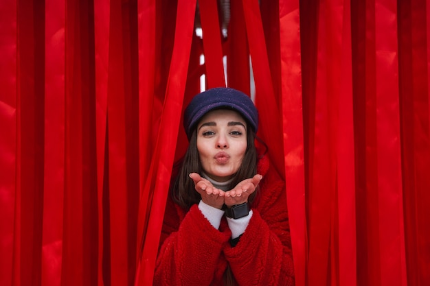 Obraz całkiem młoda kobieta wychodzi między czerwoną zasłoną.