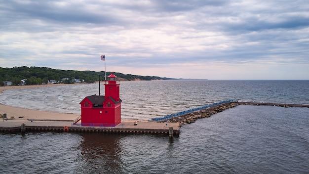 Obraz czerwonej latarni morskiej na wielkich jeziorach z falami i wybrzeżem plaży