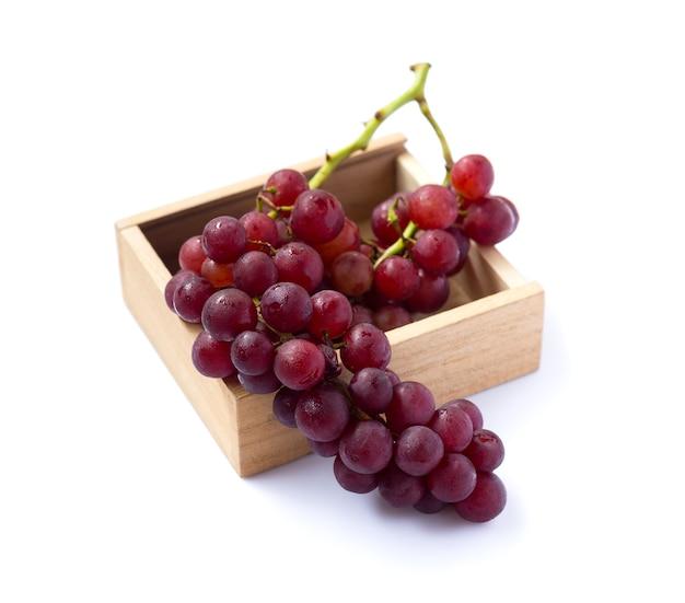 Obraz czerwonych winogron w drewnianym pudełku na białym tle