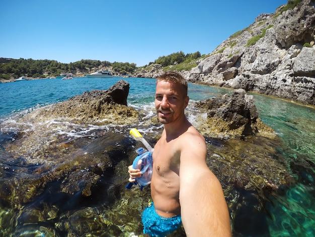 Obraz częściowo zamazany z powodu kropel wody. młody męski odkrywca w przygodzie gotowy do snorkelingu. selfie zrobione w letni dzień na skale na środku morza.