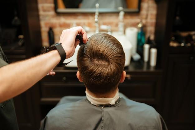 Obraz człowieka coraz strzyżenie przez fryzjera nożyczkami siedząc w fotelu.