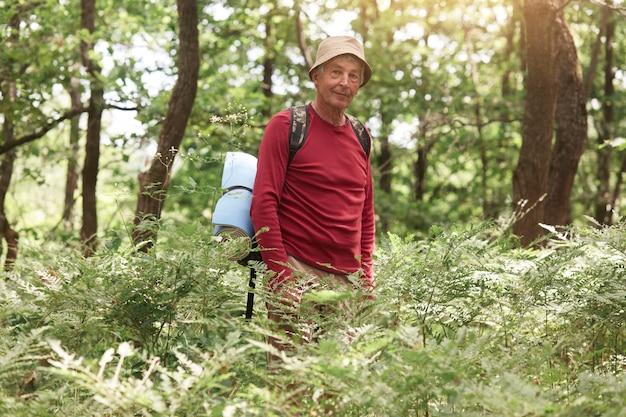 Obraz dobrze zorganizowanego przystojnego starego turysty przebywającego samotnie w lesie, spędzającego wolny czas z przyjemnością
