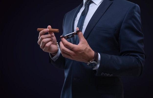 Obraz dorosłego, stylowego mężczyzny w garniturze z cygarem. koncepcja klubów cygarowych. różne środki przekazu