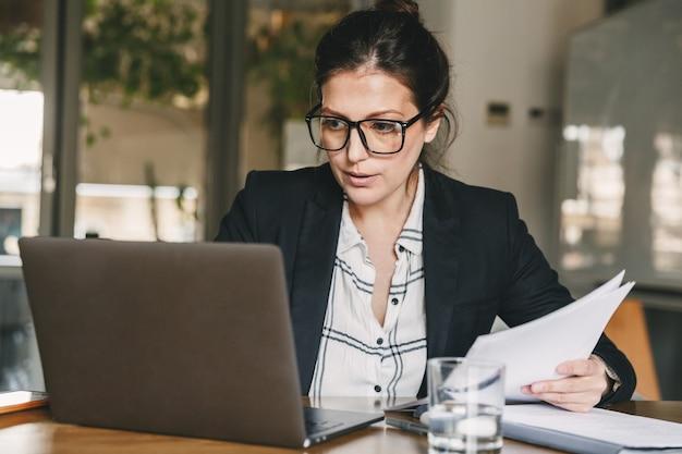 Obraz dorosłej zapracowanej kobiety 30s noszącej formalne ubrania i okulary, pracującej w biurze z laptopem i papierowymi dokumentami, siedząc przy stole