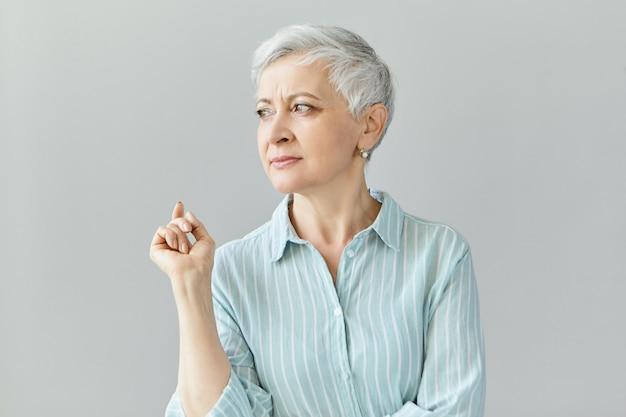 Obraz doświadczonej bizneswoman odnoszącej sukcesy w niebieskiej koszuli w paski, odwracającej wzrok z zamyślonym, poważnym wyrazem twarzy, podnosząca palec wskazujący, myśląca o korzyściach finansowych z kontraktów biznesowych