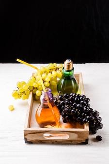 Obraz drewnianej tacy z zielonymi i czarnymi winogronami, dwie butelki soku