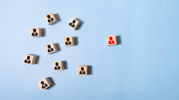 Obraz drewnianych klocków z ikonami ludzi na miętowym stole, budowanie silnego zespołu, zasobów ludzkich i koncepcji zarządzania.
