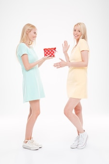 Obraz dwóch młodych szczęśliwych kobiet z prezentem na białej ścianie