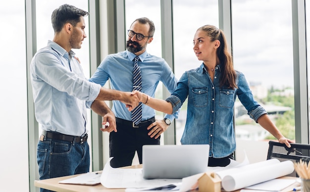 Obraz dwóch partnerów biznesowych udany uścisk dłoni razem przed przypadkowym biznesmenem w nowoczesnym biurze