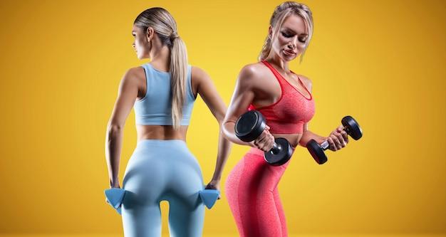 Obraz dwóch sportowych seksownych dziewczyn na żółtym tle. jeden sportowiec ubrany jest w niebieski garnitur, drugi w różowy. koncepcja fitness. wysoka jakość