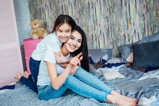 Obraz dwóch szczęśliwych małych i starszych sióstr siedzących na łóżku w pokoju.