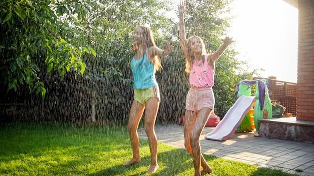 Obraz dwóch szczęśliwych roześmianych nastoletnich dziewcząt skaczących i tańczących pod ciepłym letnim deszczem w ogrodzie przydomowym domu. rodzinna zabawa i zabawa na świeżym powietrzu latem