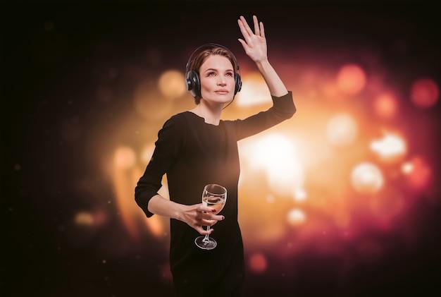 Obraz dziewczyny w czarnej sukience z lampką wina w ręku w nocnym klubie. profesjonalne słuchawki. koncepcja strony. różne środki przekazu
