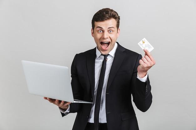 Obraz ekstatycznego brunetki biznesmena w formalnym garniturze zaskakujący, trzymając laptopa i kartę kredytową na białym tle