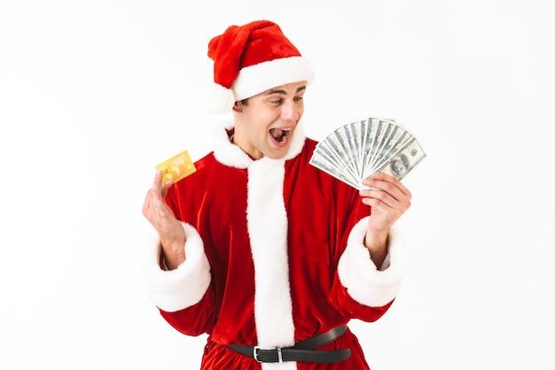 Obraz ekstatycznego mężczyzny 30s w stroju świętego mikołaja trzymającego dolary i kartę kredytową