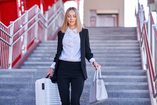 Obraz eleganckiej kobiety spacerującej z torbą i walizką na dworcu kolejowym