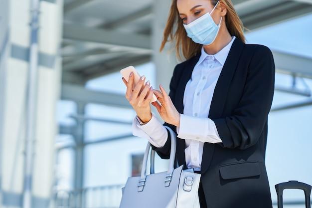 Obraz eleganckiej kobiety w masce ochronnej spacerującej z torbą i walizką na stacji kolejowej