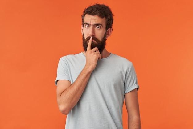 Obraz emocji przystojnego młodego faceta, poważny i pewny siebie, z palcem dotykającym nosa stojącego
