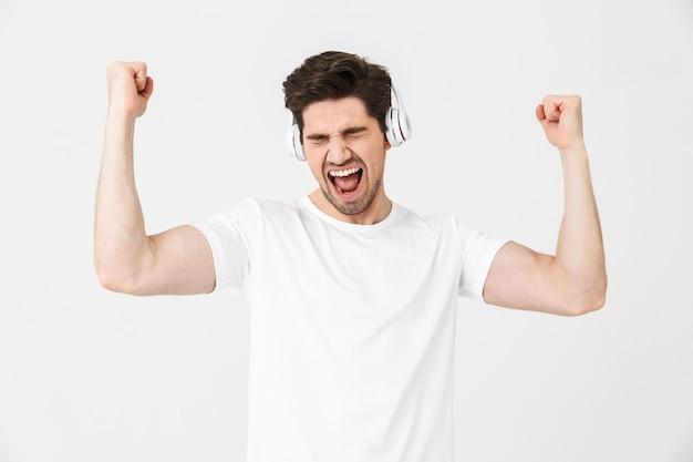 Obraz emocjonalnego podekscytowany młody człowiek pozowanie na białym tle nad białą ścianą słuchania muzyki w słuchawkach zrobić gest zwycięzcy.