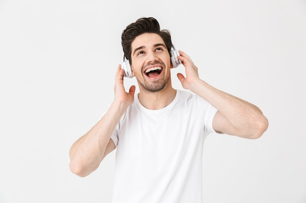Obraz emocjonalnego podekscytowany młody człowiek pozowanie na białym tle nad białą ścianą słuchania muzyki w słuchawkach.